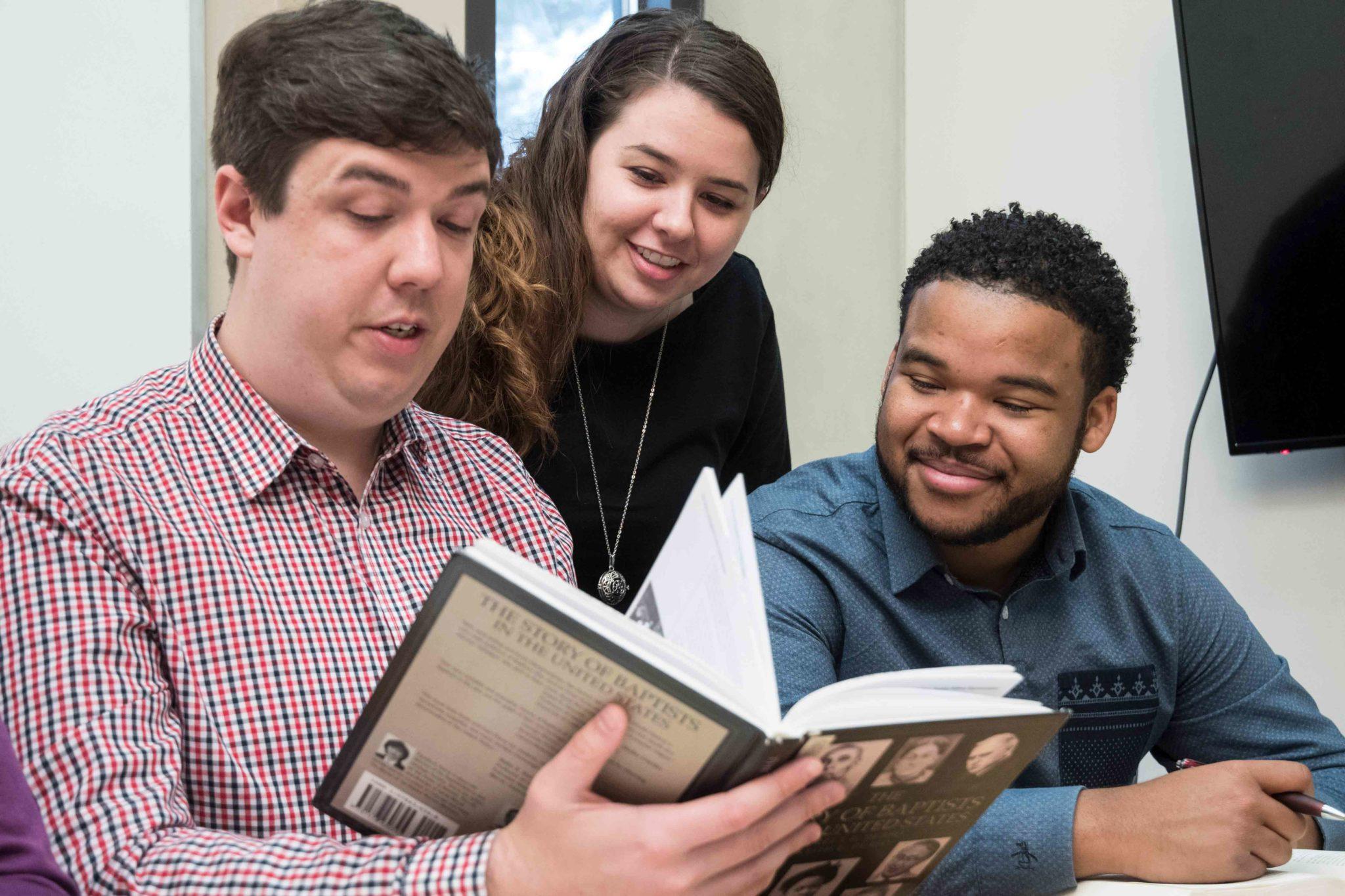 Three students look at a book.
