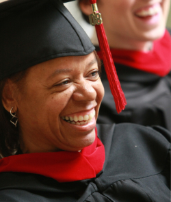 A graduate wearing a cap and gown smiles