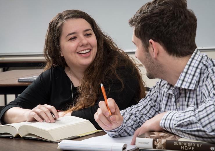 Two theology students sit at a desk