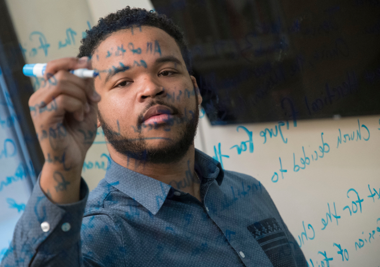 A McAfee theology students writes on a glass window with blue marker.